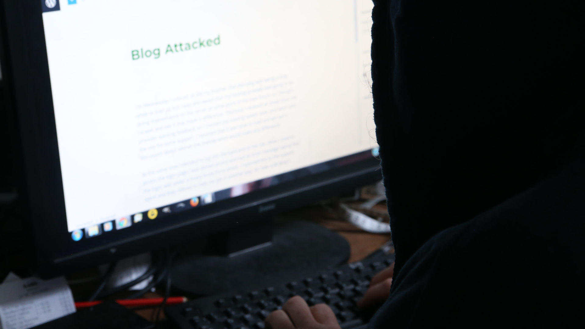 Hooded person in front of computer screen